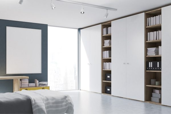 Corner of a bedroom with a home office, a double bed , a table with a drawer beside it, a large rectangular poster is hanging on a gray wall and a tall bookcase. 3d rendering. Mock up.